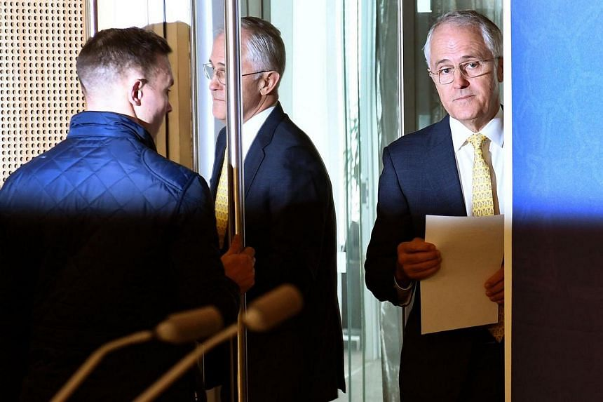 Australia's Prime Minister Malcolm Turnbull (right) arrives at a press conference in Sydney on July 3, 2016.