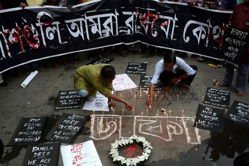 Indian activists light candles during prayers for the Dhaka terror attack victims, in Calcutta.