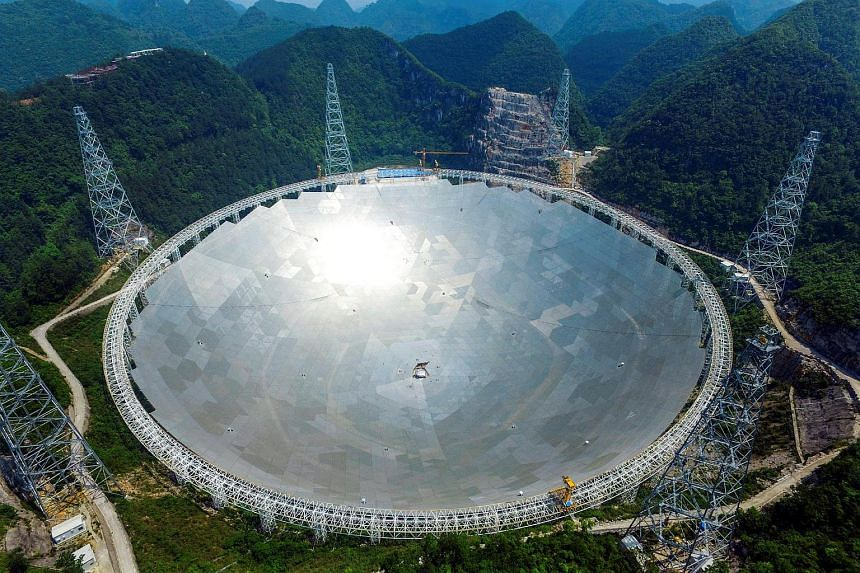 The 500-metre  aperture spherical telescope (FAST) is seen at the final stage of construction, among the mountains in Pingtang county, Guizhou province, China.
