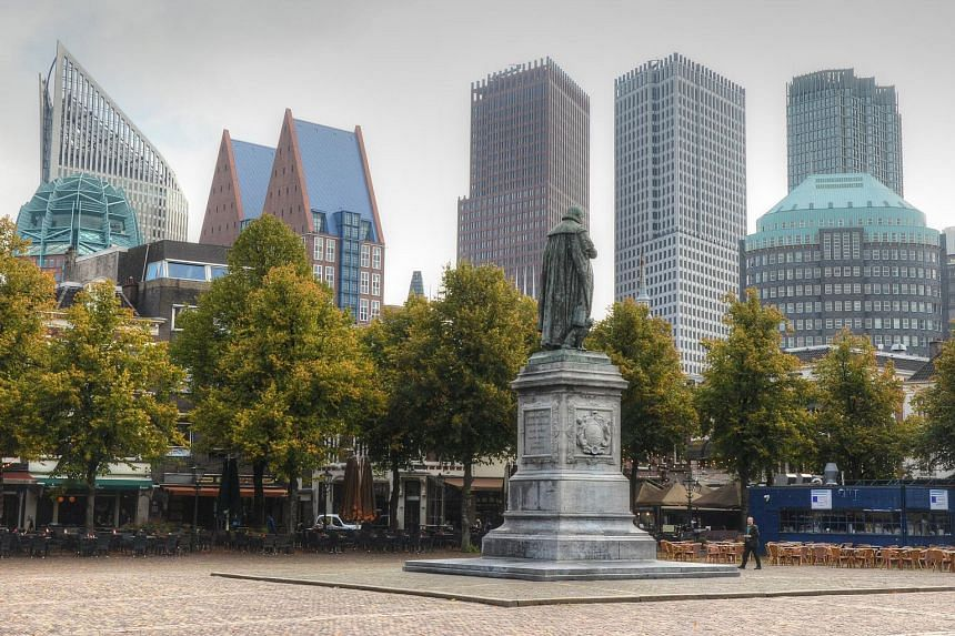 Het Plein, a famous town square in the The Hague, is photographed with the city's skyline in the background.