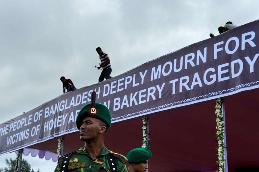 A Bangladeshi soldier stands guard as workers put the finishing touches to a banner before a memorial service in Dhaka, on July 4, 2016.