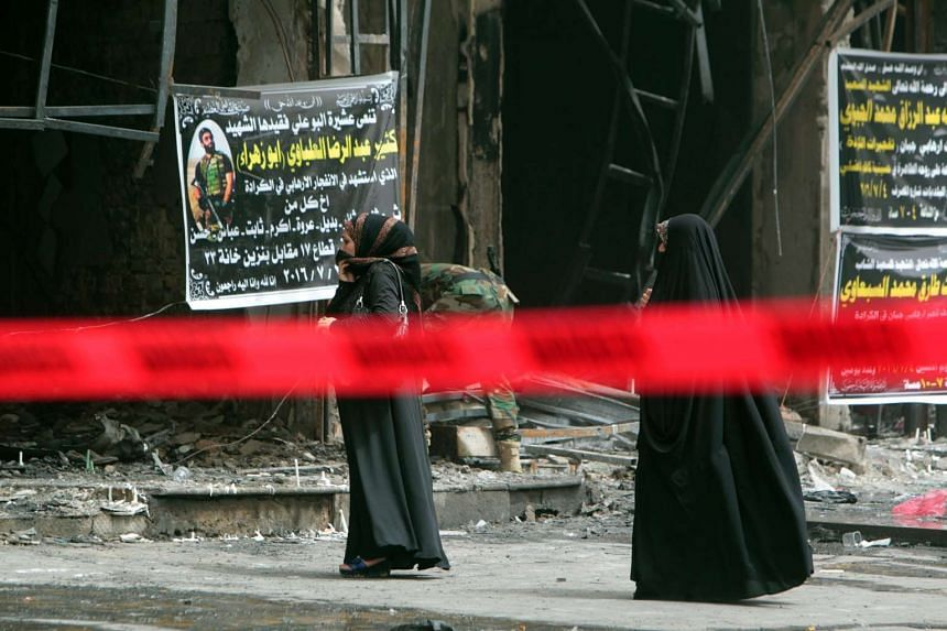Iraqi women stand at a site barricaded with a security red tape in Baghdad's Karrada neighbourhood, on July 4, 2016, after an attack took place.