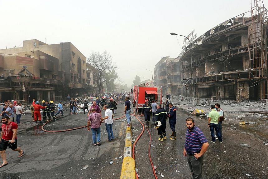 Shocked Iraqis at the site of the suicide car bombing in Baghdad's central Karrada district yesterday. At least 125 people were killed and 200 others were wounded in the suicide attack.