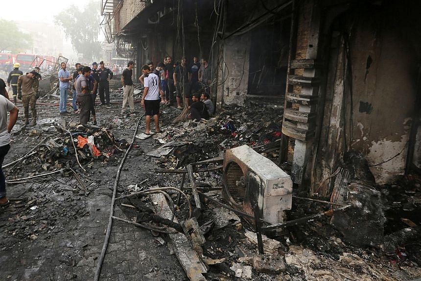 Iraqis inspecting the damage at the site of a suicide car-bomb explosion yesterday in Baghdad's central Karrada district. The blast, which ripped through an area where many people go to shop ahead of the holiday marking the end of the Muslim fasting