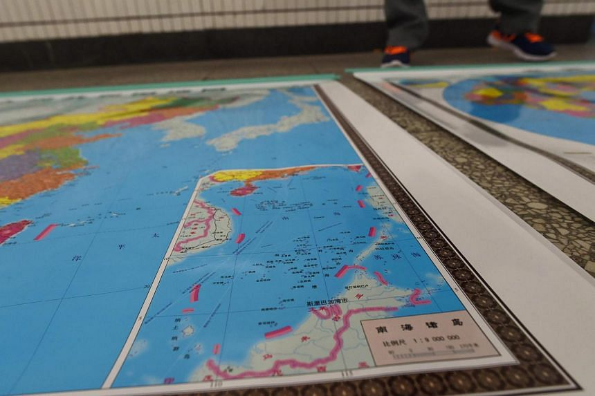 A vendor stands behind a map of China including an insert with red dotted lines showing China's claimed territory in the South China Sea on June 15.