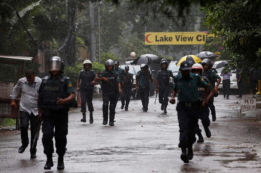 Policemen patrol on the road leading to the Holey Artisan Bakery where gunmen attacked.