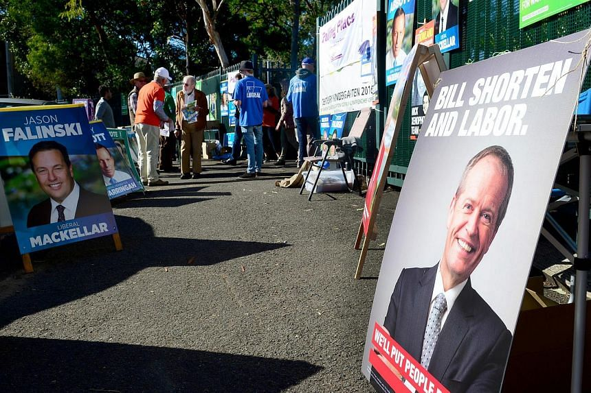 Campaign posters of various candidates stand as voters enter a polling station in Sydney, Australia, on July 2.