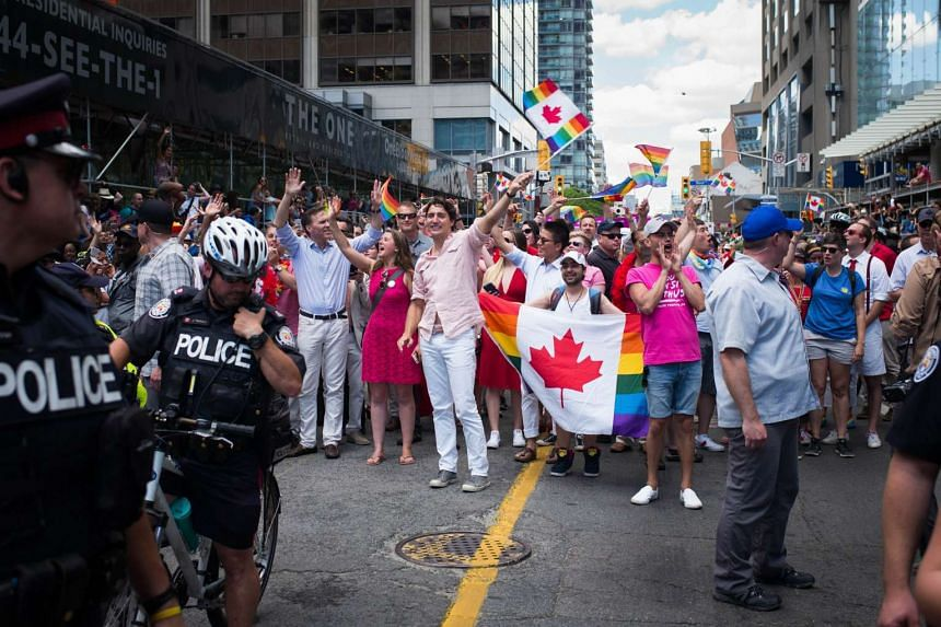 Canadian Prime Minister Justin Trudeau (middle, waving flag) made history by becoming the nation's first PM to march in the the annual Pride Festival parade on Sunday in Toronto.