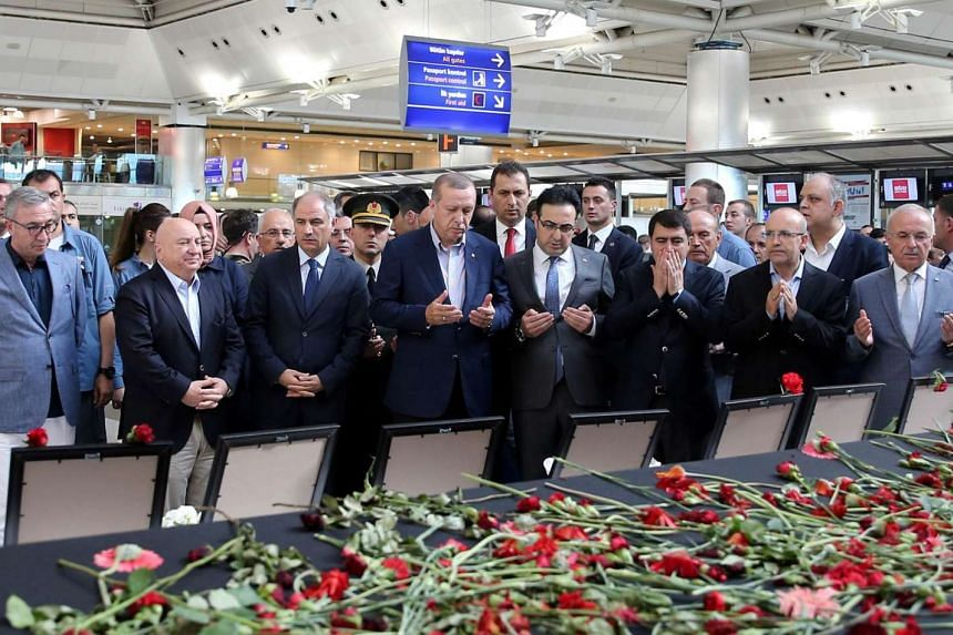 ​Turkish President Recep Tayyip Erdogan (centre) praying near flowers and portraits of the victims of the Istanbul Ataturk Airport attack on July 2.