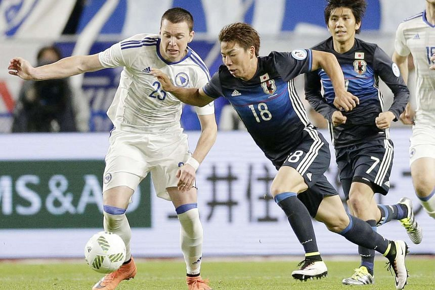 Takuma Asano (center) dribbles the ball before Bosnia and Herzegovina's midfielder Haris Duljevic (left) while Japan's midfielder Yosuke Kashiwagi (right) looks on during their Kirin Cup soccer 2016 final match in Suita city, Osaka prefecture on June