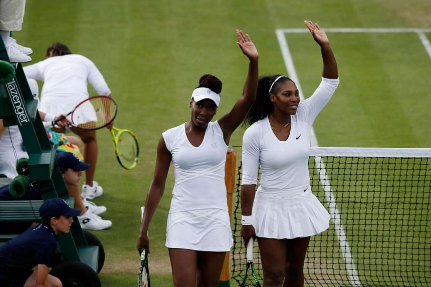 Serena Williams (right) and Venus Williams wave to the crowd after winning the women's doubles first round match at the 2016 Wimbledon Championships, on June 30, 2016.