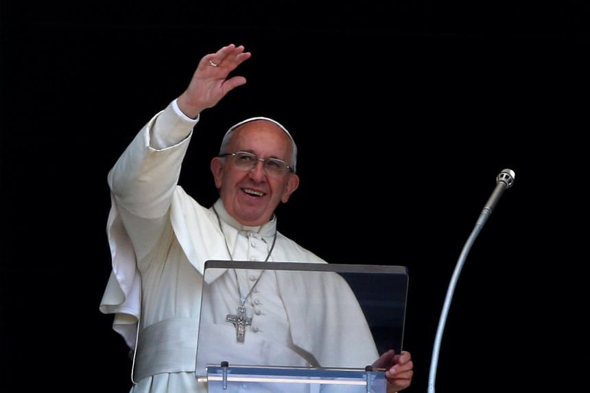 Pope Francis waves during his Sunday Angelus prayer in St Peter's square at the Vatican, on July 3, 2016.