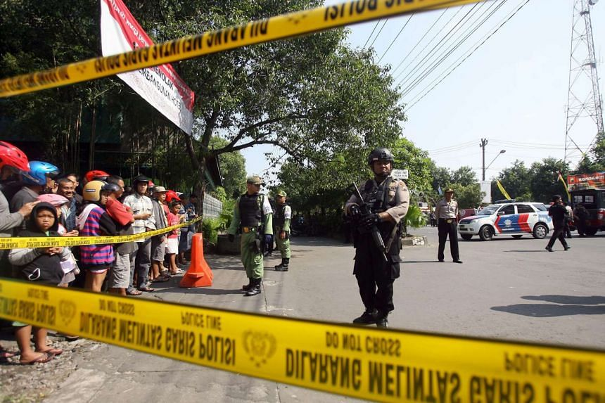 Indonesian police officers stand guard after a suicide bomb attack at the police headquarters in Solo, Indonesia, on July 5, 2016.