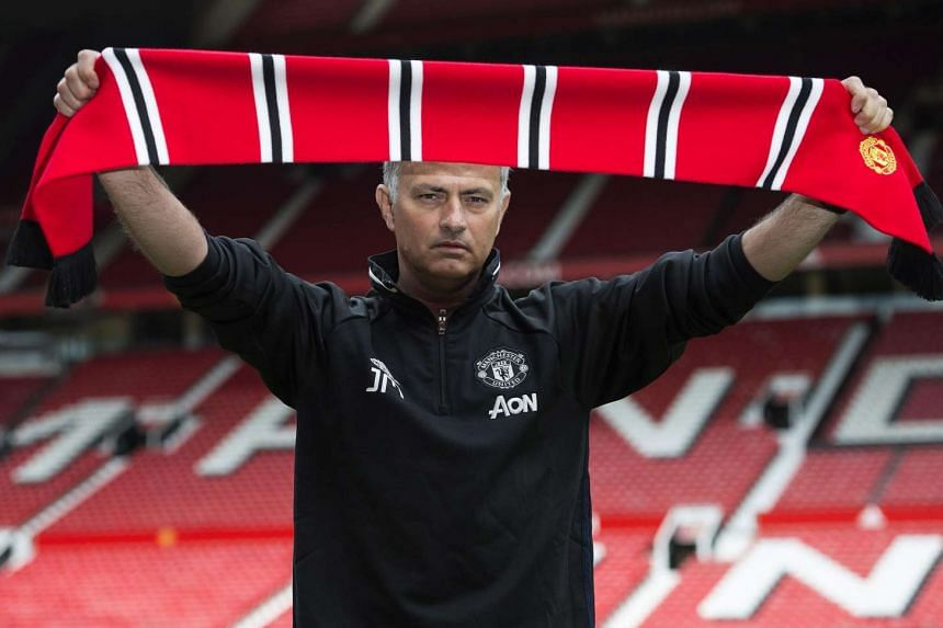 Manchester United's new manager Jose Mourinho poses with a scarf on the pitch at Old Trafford stadium in Manchester, on July 5, 2016.