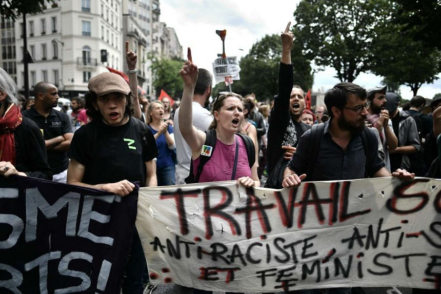 """People hold a banner reading """"Work, anti-racist and feminist"""" during a labour reform protest in Paris on July 5, 2016."""
