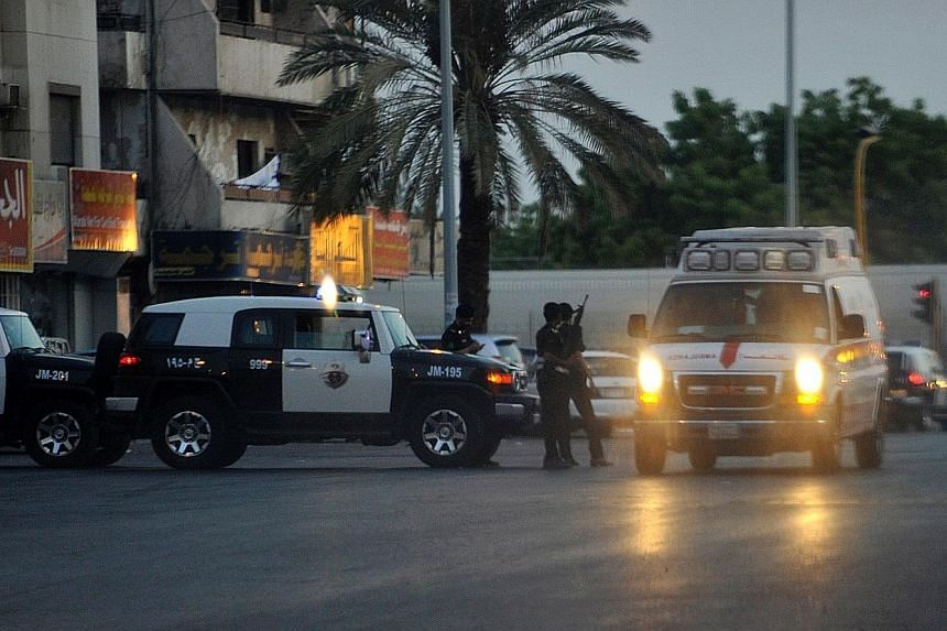Police officers at the site of the suicide bombing in Jeddah yesterday. The attacker parked his car near the US consulate and detonated his device after two guards approached him, killing him and injuring them.