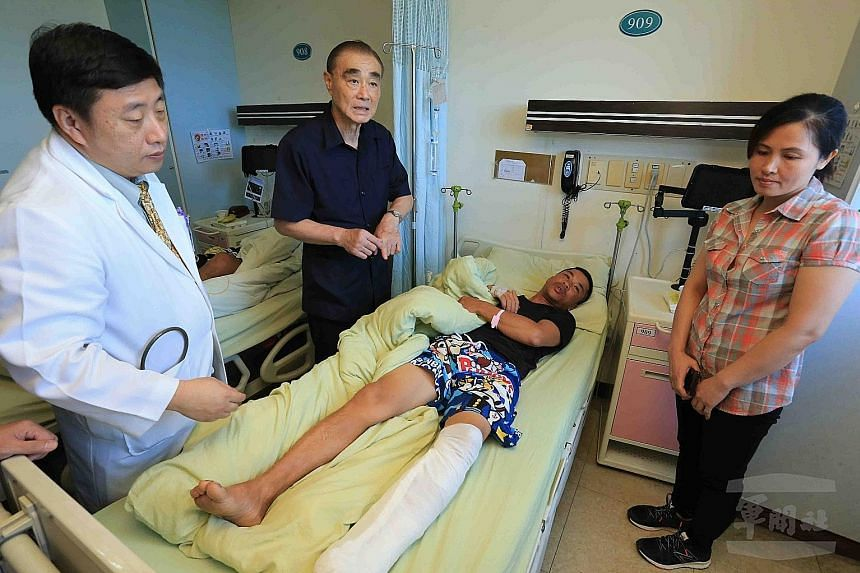 A fisherman injured by the misfired navy missile receiving a visit from Taiwanese Defence Minister Feng Shih-kuan (second from left) at a hospital in Kaohsiung at the weekend. Mr Feng apologised for the incident and promised to tighten discipline and