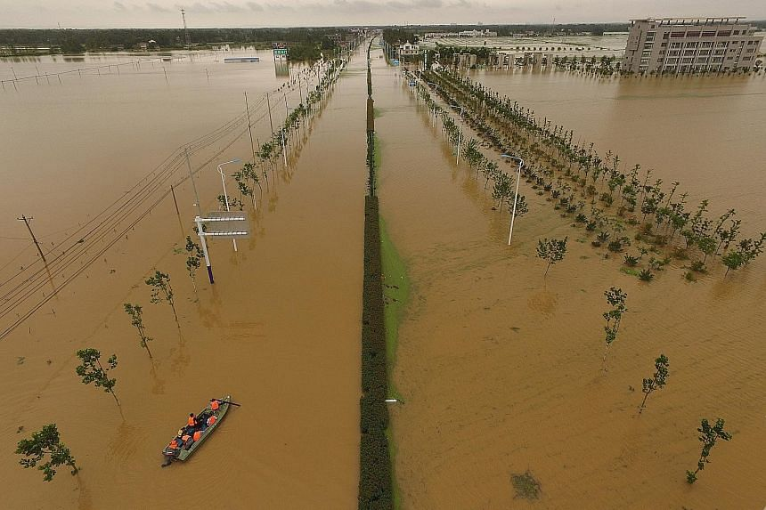 Rescuers looking for survivors in flood-hit Shucheng county in China's eastern province of Anhui on Sunday. Torrential rain in the province has left 27 people dead and three missing, said the local authorities yesterday. Continuous rainfall over the