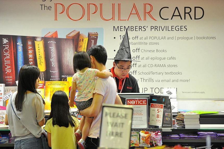 Promotional materials and merchandise on Harry Potter on display at Popular's Bras Basah Complex outlet; and a staff member donning a wizard hat (above).