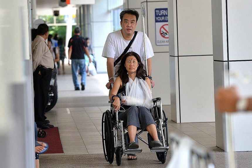 (Above)  Madam Chua in a wheelchair at National University Hospital yesterday. She was there for treatment.