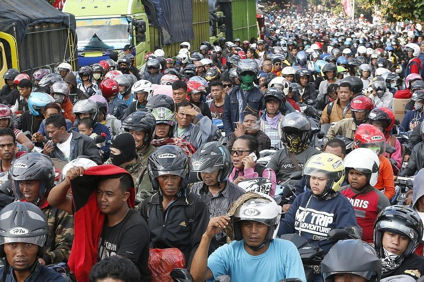 Indonesian motorcyclists prepare to board a ferry in Bali on Sunday ahead of the Eid al-Fitr festival tomorrow, also called Lebaran in Indonesia and Hari Raya Puasa in Malaysia. Millions of Muslims head to their home towns in the annual migration, pa