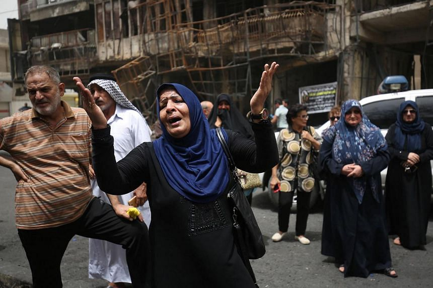 Iraqis react at the site of a suicide-bombing attack which took place in Baghdad's Karrada neighbourhood on July 4, 2016.