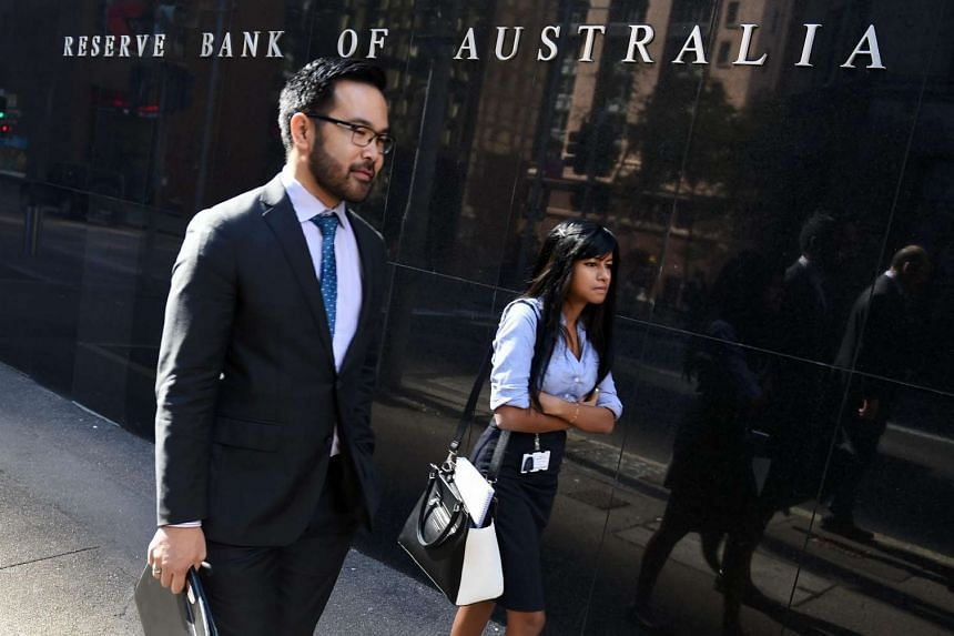 People walk past the Reserve Bank of Australia building in Sydney on May 3.