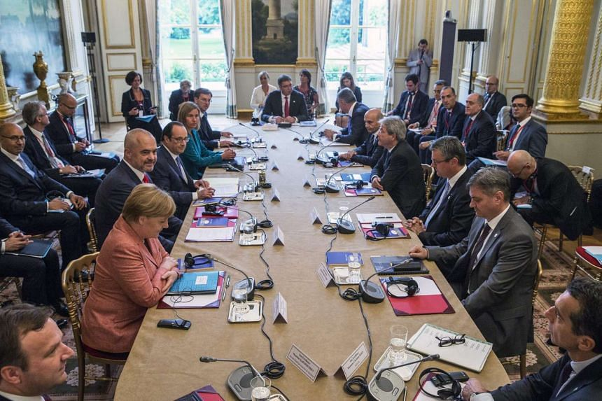 Delegations from the Balkans sit around a table with French President Francois Hollande (fourth from left) and German Chancellor Angela Merkel (second from left) during the Balkan summit hosted by France at the Elysee Palace in Paris, France on July