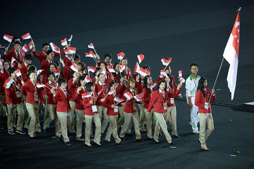 The Singapore contingent led by flag-bearer, hurdler Dipna Lim-Prasad, and chef de mission Annabel Pennefather marching past the grandstand at the opening ceremony of the 27th SEA Games.