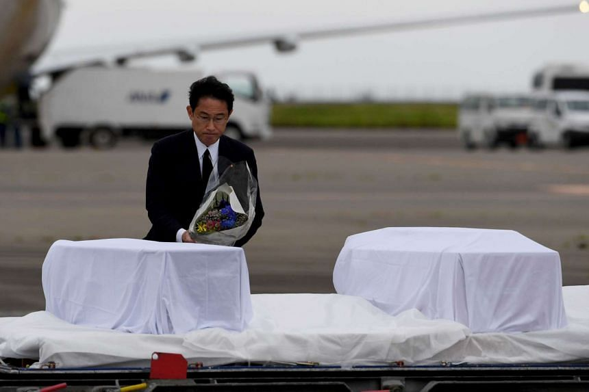 Japanese Foreign Minister Fumio Kishida places a bouquet of flowers among the coffins of Japanese victims upon their arrival at Tokyo International Airport on July 5, 2016.