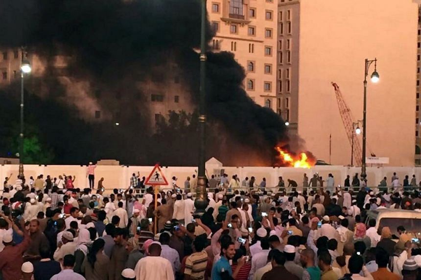 Muslim worshippers gather after a suicide bomber detonated a device near the security headquarters of the Prophet's Mosque in Medina, Saudi Arabia, on July 4, 2016.