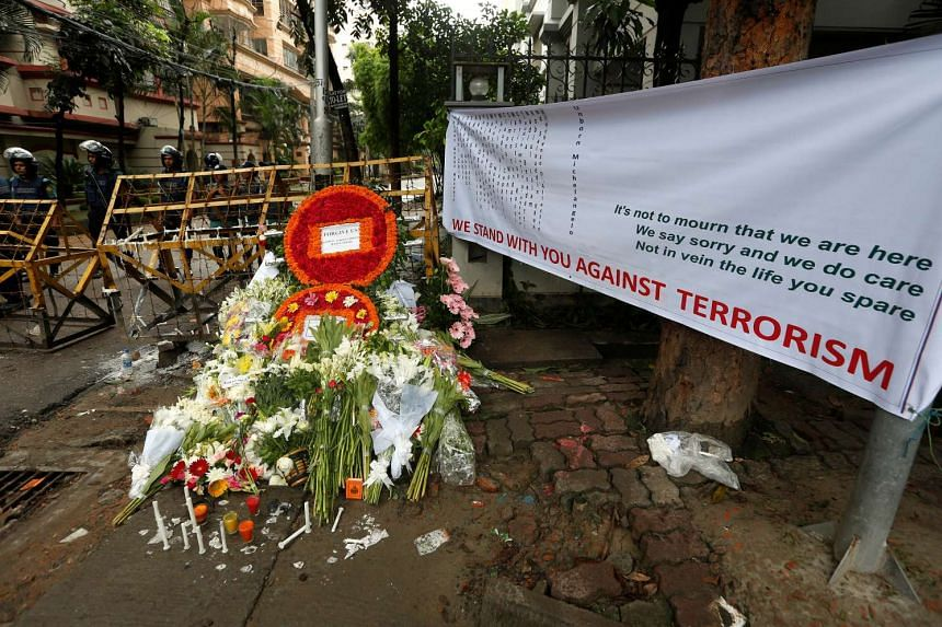 Wreaths and flowers, offered by people to pay tribute to the victims of the Bangladesh attack, at a makeshift memorial near the attack site, in Dhaka, on July 5, 2016.