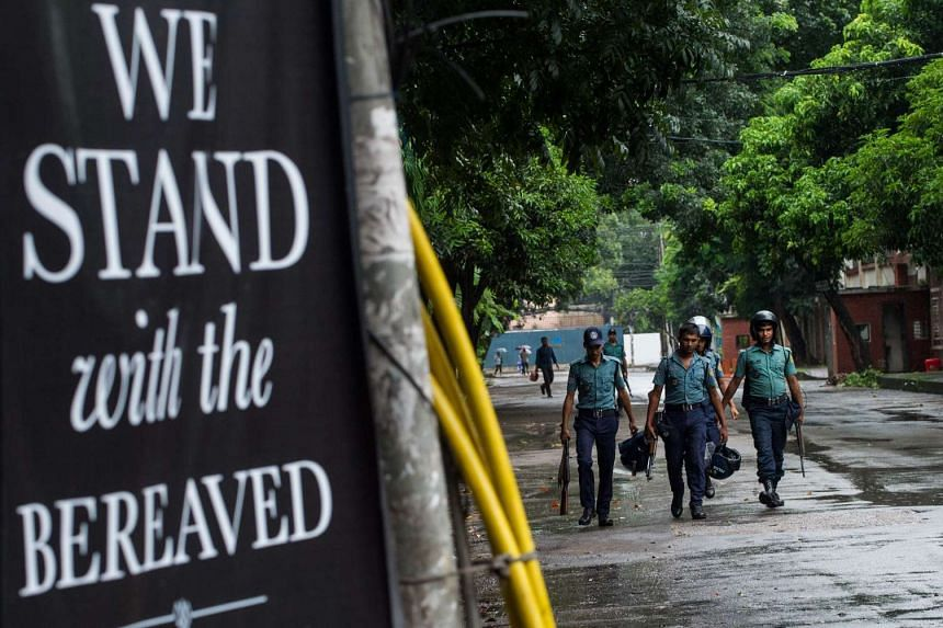 """Bangladeshi policemen walk near a banner that reads """"We stand with the bereaved"""" near an upscale restaurant on July 5, 2016."""
