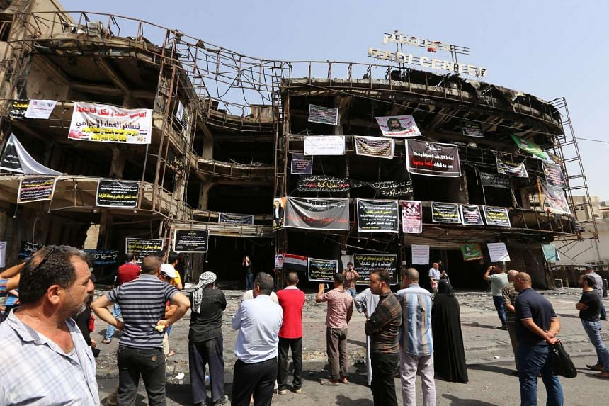 Relatives of victims gather on July 5, 2016, at the site of a suicide-bombing attack which took place in the Karrada neighbourhood of Baghdad.