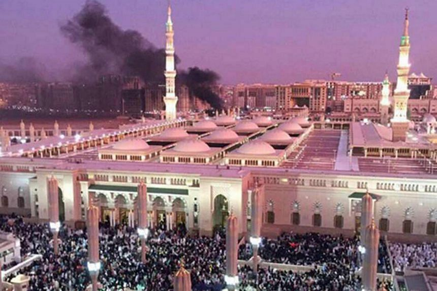 The Prophet's Mosque with smoke rising in the background in the holy city of Medina, in Saudi Arabia, on July 4.