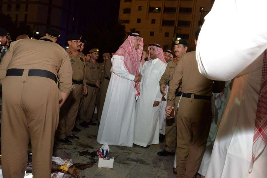 Saudi Emir of Medina Faisal bin Salman bin Abdulaziz (centre-left) and security officers inspect the site of the suicide attack near the security headquarters of the Prophet's Mosque in Medina City on July 4.