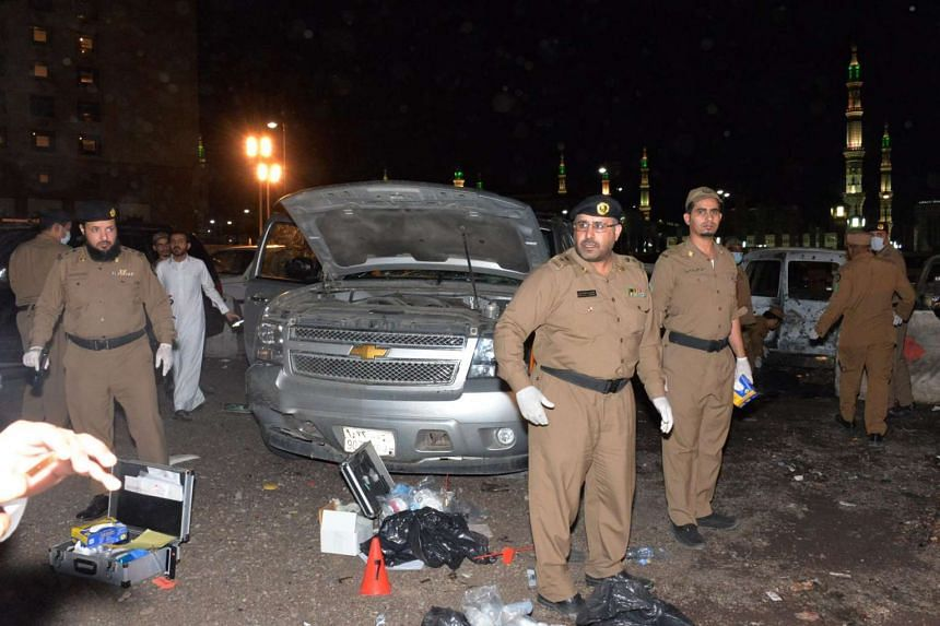Saudi security personel gather at the site of the suicide attack near the security headquarters of the Prophet's Mosque in Medina City on July 4.