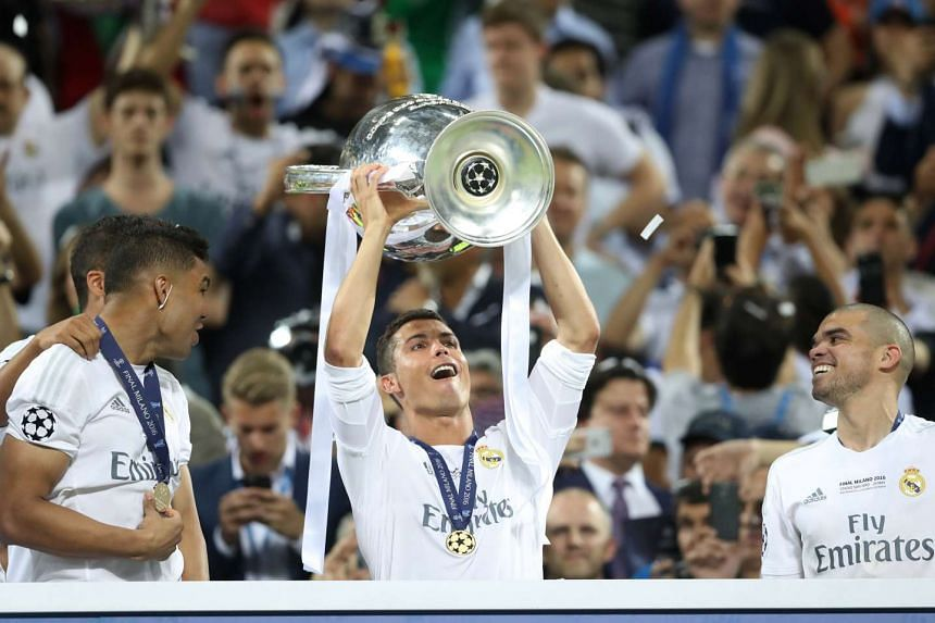 Real Madrid's Cristiano Ronaldo celebrates with the trophy after winning the UEFA Champions League. The European Union has ordered it, and six other Spanish football clubs to pay back millions of euros in illegal state aid.