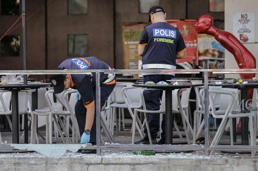 Malaysian police officers of the forensic department investigate the scene of a bomb explosion in Puchong, Selangor.