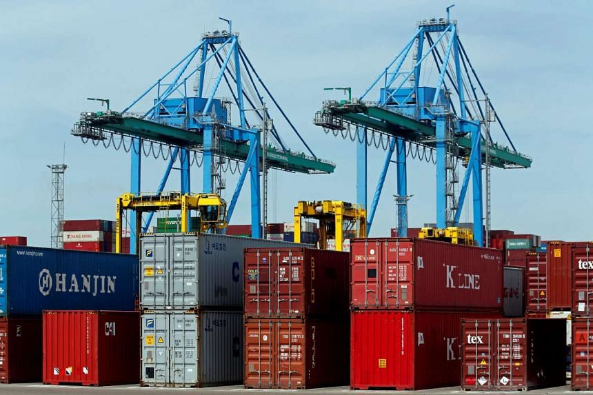 Cranes move shipping containers stacked along the dockside at the Seayard Co. terminal in Fos sur Mer, France.