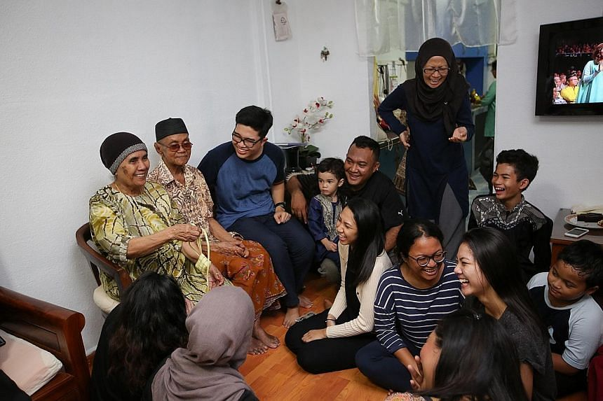 Madam Suryani (standing) and her family spanning four generations having a merry time at the flat of her grandparents - Mr Yasin Karim, 90, and Madam Siti Jibah, 84 (both seated) - yesterday.
