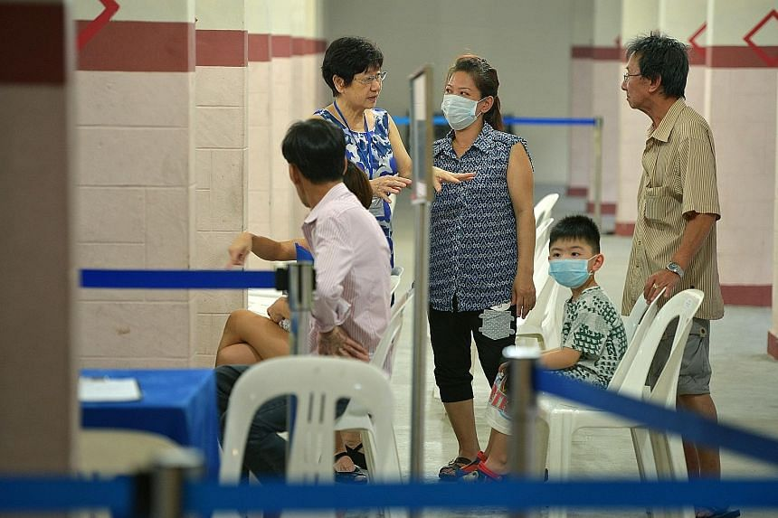 Residents of Block 203, Ang Mo Kio Avenue 3, getting screened for tuberculosis last month. Many seniors happen to live in the block where the discovery of a highly unusual cluster of six drug-resistant TB cases triggered the screening exercise.