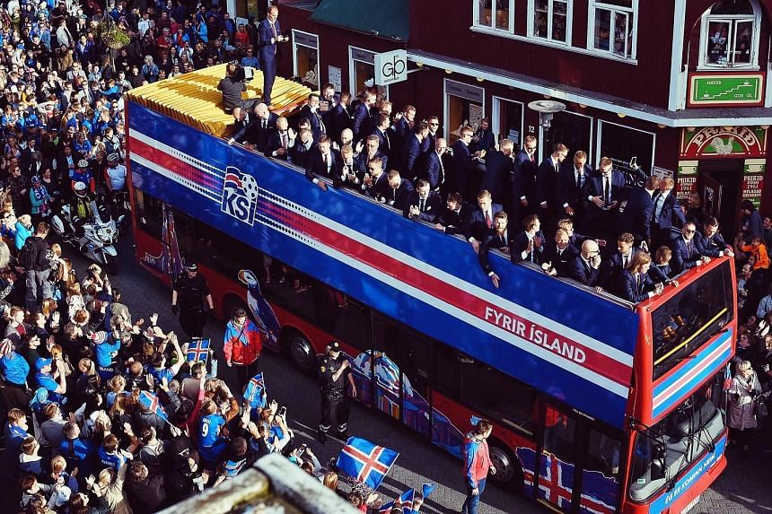 Members of the Iceland team are feted by fans as they are taken through the streets of Reykjavik, the national capital, on an open-top bus on Monday on their return from Euro 2016. The smallest nation at the tournament had stunned fans and pundits by