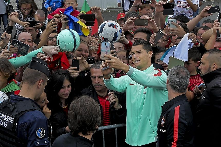 Top: Portugal superstar Cristiano Ronaldo takes a wefie as he is surrounded by supporters who must surely be concerned about their team's inability to win a game in regulation time. Above: Wales talisman Gareth Bale signs autographs for fans.