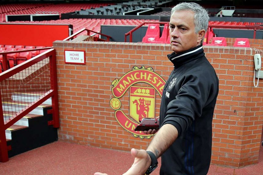 Mourinho poses for pictures during a media conference at Old Trafford on July 5, 2016.