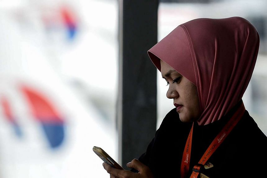 A Malaysian woman checks her mobile phone as Malaysia Airlines aircraft are parked on the tarmac at the Kuala Lumpur International Airport in Sepang on June 20, 2016.