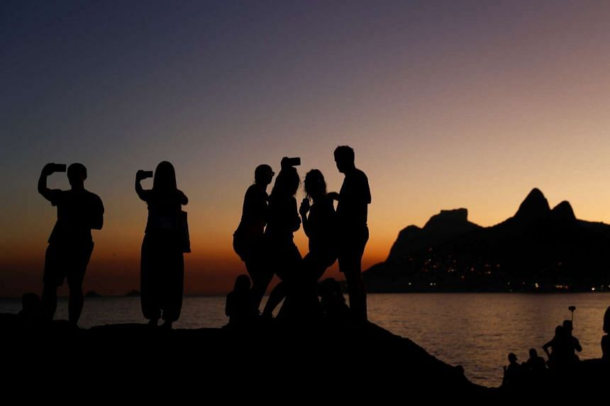 People taking selfies during sunset on the rocks of Arpoador beach in Rio de Janeiro, Brazil, on July 4, 2016.
