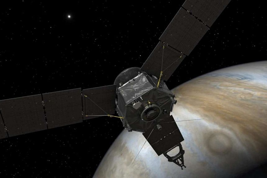 An artist's rendering of Nasa's Juno spacecraft at Jupiter, with its solar arrays and main antenna pointed toward the distant sun and Earth.