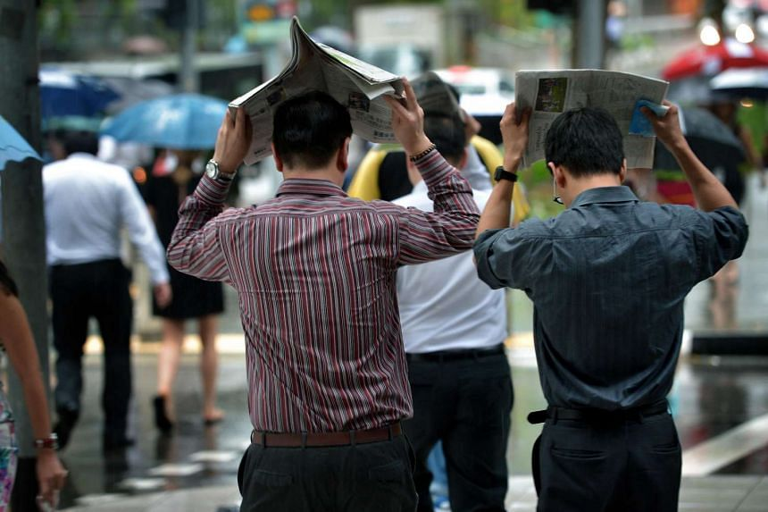Office workers caught without an umbrella during a sudden downpour at Raffles Place on Feb 24.