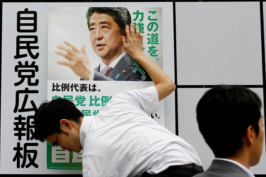 A staff member of Japan's ruling Liberal Democratic Party (LDP) posts a poster for the July 10 upper house election with the image of Shinzo Abe, Japan's Prime Minister.